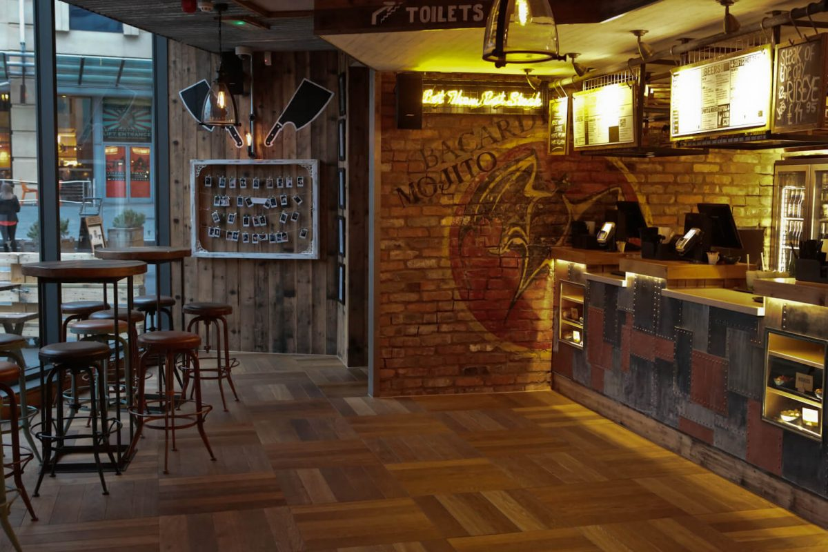 Just love all the exposed brick, wood and metal in this funky industrial Son of Steak interior