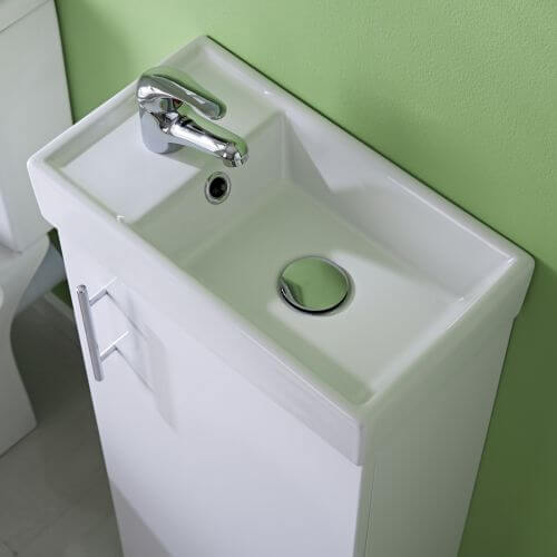 Closeup of floorstanding short projection cloakroom basin / sink with vanity in small bathroom ensuite