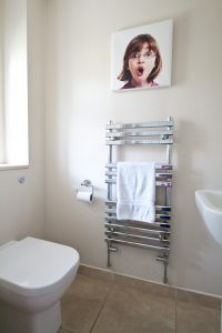 Our Cloakroom with cloakroom basin, chrome towel rail and back-to-wall wc