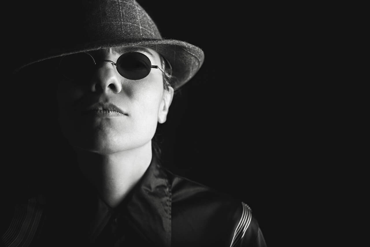 Black and white photo of a female spy with hat and dark glasses on