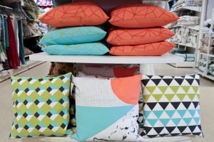 HomeSense Summer Trends Graphic : A collection of cushions in cyan, orange and multicoloured geometric prints