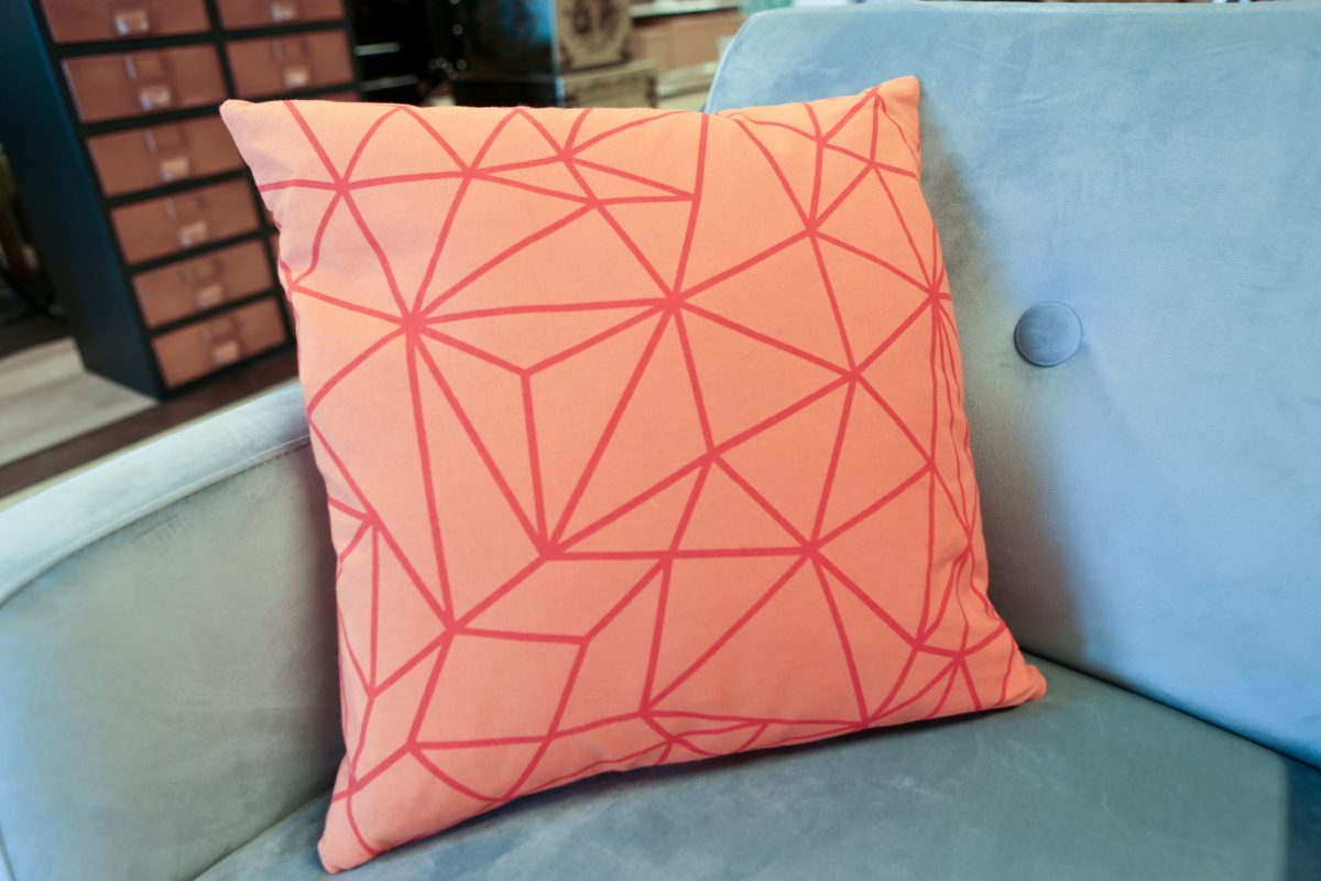 HomeSense Summer Trends Graphic Bright orange geometric cushion on a velvet blue chair