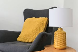 Mustard lamp, grey armchair and mustard cushion