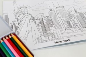 Colouring book featuring New York and a set of colouring pencils in a tin