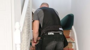 Carpet fitter fitting underlay on our stairway