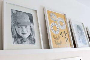 Photos and prints work well with Finished Gallery wall using Ikea Mosslanda Picture ledges